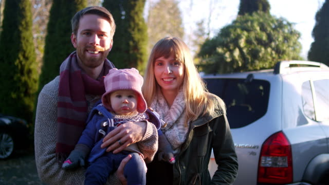 Portrait-of-a-young-mother-father-and-baby-in-front-of-their-car-with-Christmas-tree-on-top