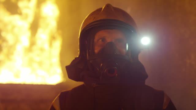 Retrato-de-un-bombero-valiente-de-pie-en-un-incendio-edificio-ardiente-furioso-detrás-de-él-Abre-llamas-y-humo-en-el-fondo-