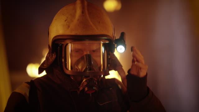 Edificio-está-en-llamas-Valiente-totalmente-equipados-los-bomberos-saca-su-casco-Llamas-en-el-fondo-Cámara-lenta-