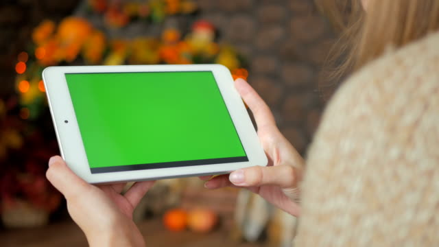 Woman-looking-at-tablet-computer-with-green-screen