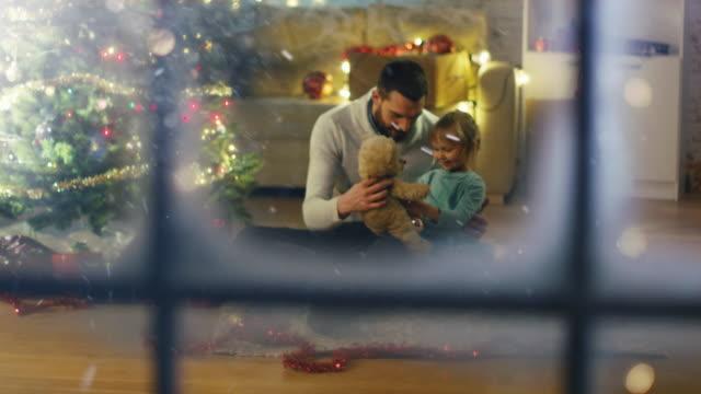 Mirando-a-través-de-Snowy-Window-Sentado-bajo-Navidad-tres-padre-y-la-hija-juegan-con-el-oso-de-peluche-
