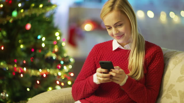 Beautiful-Blonde-Woman-Sits-on-a-Couch-and-Uses-Smartphone-Christmas-Tree-and-Room-Decorated-with-Lights-are-in-the-Background-