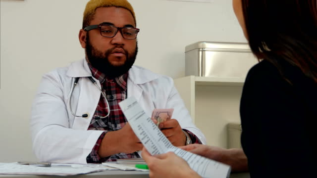 Male-doctor-putting-money-in-his-pocket-paid-by-female-patient-for-medical-visit