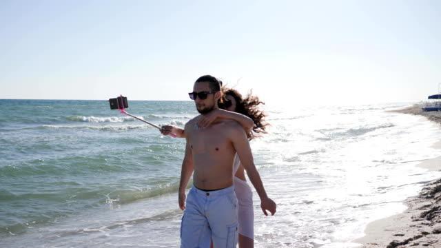 Luna-de-miel-feliz-pareja-divertirse-en-viajes-niña-alegre-saltando-sobre-la-espalda-del-chico-Foto-tomar-autofe-arena-brillante-pareja-de-vacaciones-zonas-tropicales