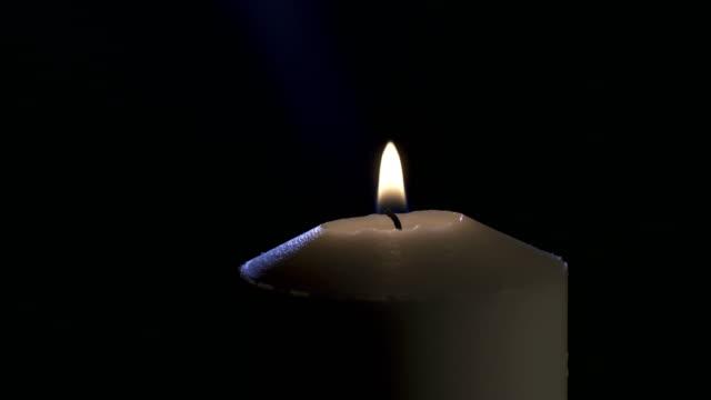 Imágenes-de-macro-lenta-de-una-vela-blanca-sobre-un-fondo-oscuro