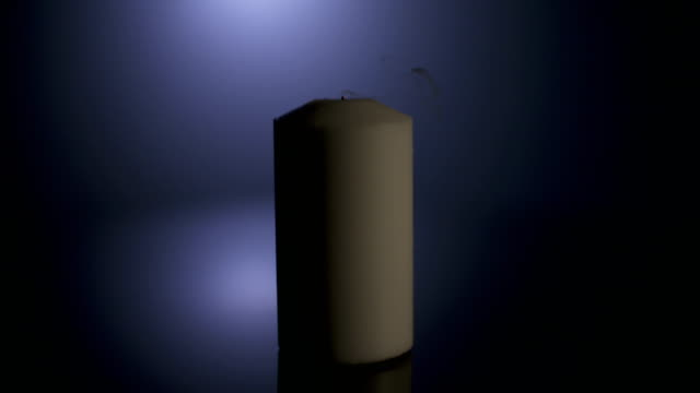 Slow-motion-macro-footage-of-a-white-candle-on-a-dark-background