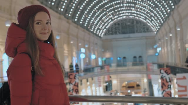 beautiful-young-woman-is-walking-through-the-big-shopping-mall-in-Moscow-Blurry-background-with-beautiful-lights-