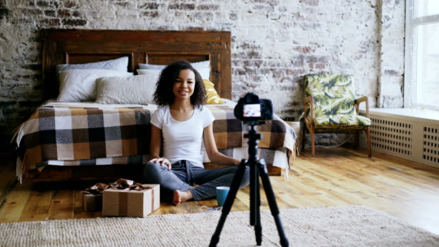 Young-cheerful-mixed-race-girl-recording-video-blog-about-packing-christmas-gift-box-at-home