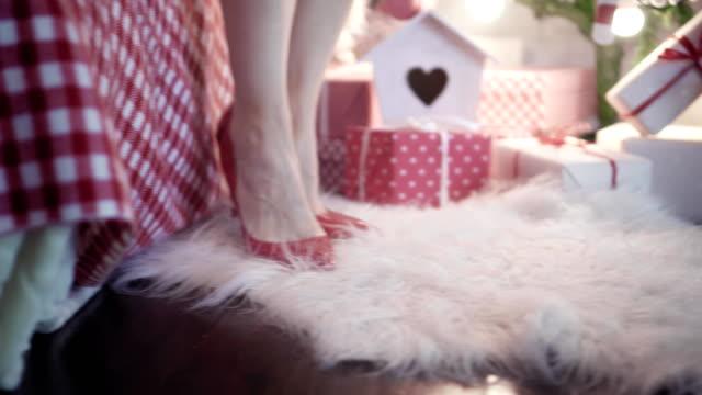 una-joven-hermosa-es-caminar-en-los-zapatos-de-tacón-rojo-cerca-del-árbol-de-Navidad-se-sienta-en-la-cama-y-saca-sus-zapatos-Vista-de-clos-de-piernas