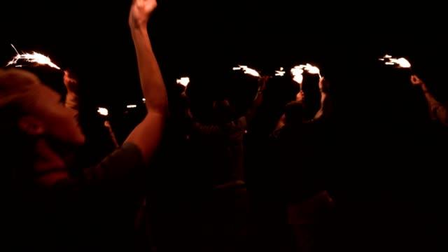 Amigos-de-joven-inconformista-multiétnica-celebrando-en-fiesta-al-aire-libre-con-luces-de-Bengala