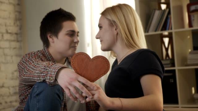 Zwei-junge-Lesben-süß-schauen-einander-mit-einem-Herzschild-in-der-Hand-Lächeln-Lachen-60fps