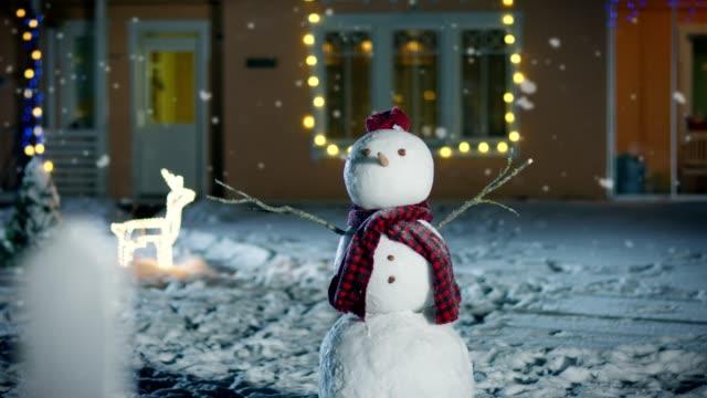 Divertido-muñeco-de-nieve-con-sombrero-y-bufanda-en-el-patio-trasero-de-la-casa-idílico-decorado-con-guirnaldas-en-la-Nochebuena-Suave-nieve-está-cayendo-en-esa-mágica-noche-de-invierno-