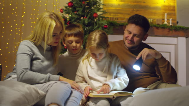 Parents-and-Kids-Reading-Fairytale-by-Christmas-Tree-at-Home