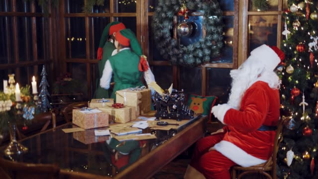 Elves-in-festive-costumes-are-dancing-around-the-table-with-gifts-candles-and-a-typewriter-in-the-presence-of-Santa-Claus-who-watching-and-setting-the-rhythm-on-the-background-of-the-New-Year-tree-near-the-window-in-the-room-