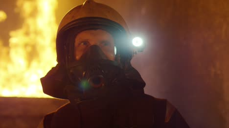 Portrait-Shot-of-a-Brave-Fireman-Standing-in-a-Burning-Building-Fire-Raging-Behind-Him-Open-Flames-and-Smoke-in-the-Background-