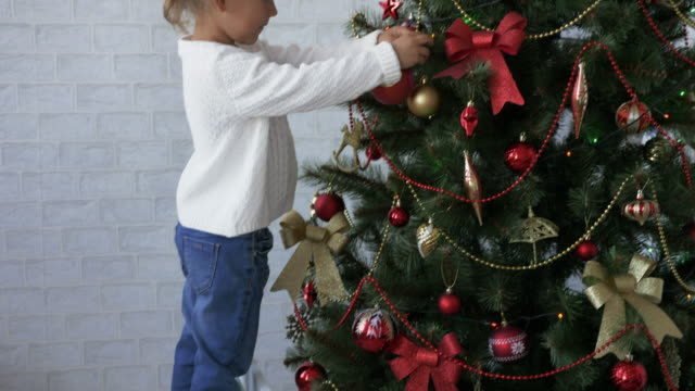 Cute-little-girl-decorates-the-Christmas-tree-