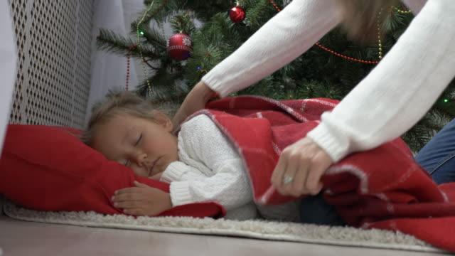 Cute-little-girl-sleeping-under-Christmas-tree-at-morning