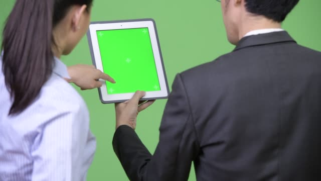 Young-Asian-business-couple-using-digital-tablet-together