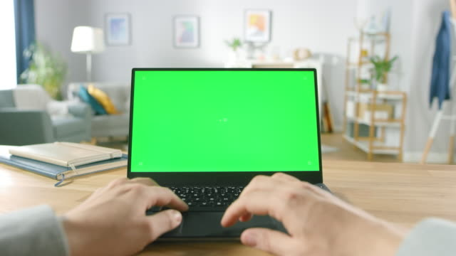 First-Person-Close-up-Shot-Man-Uses-Laptop-with-Green-Mock-up-Screen-While-Sitting-at-the-Desk-in-His-Cozy-Living-Room-