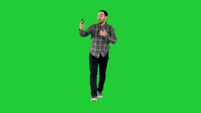 Man-calling-via-video-call-on-phone-talking-to-someone-waving-hello-during-videochat-conversation-on-a-Green-Screen-Chroma-Key