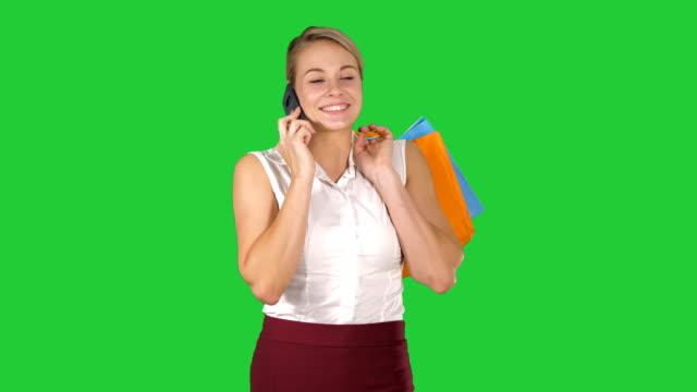 Mujer-de-compras-con-teléfono-inteligente-sosteniendo-bolsas-y-caminando-sobre-una-pantalla-verde-Chroma-Key