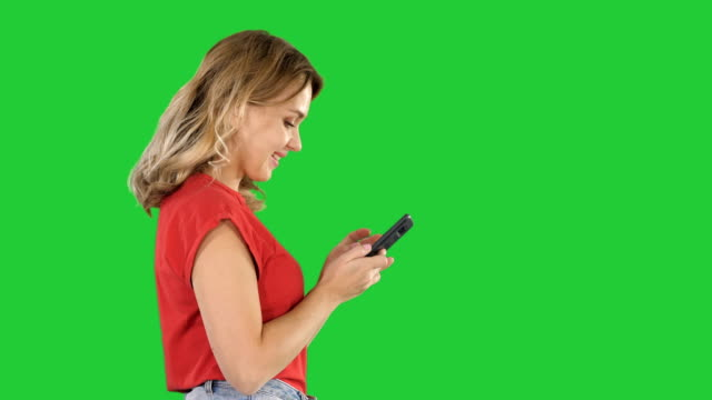 Happy-cute-beautiful-young-woman-play-games-by-mobile-phone-on-a-Green-Screen-Chroma-Key