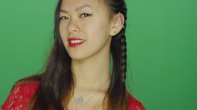Young-Asian-woman-staring-and-looking-sexy-on-a-green-screen-studio-background