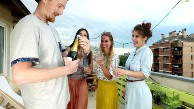 Side-view-of-hipster-man-opening-champagne-female-friends-waiting-with-glasses