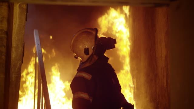Valiente-bombero-desciende-en-quema-de-escaleras-Mirando-a-su-alrededor-inspeccionando-el-edificio-Llamas-en-el-fondo-