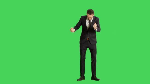 Totale-eines-schönen-lächelnden-Geschäftsmann-tanzen-Guns-Fingergeste-zu-machen-und-Spaß-haben-Hintergrund-ist-Green-Screen-