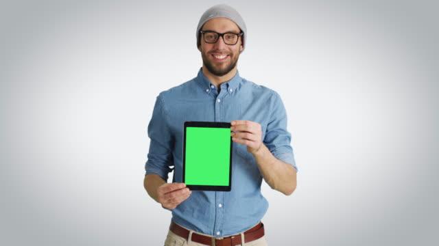Tiro-medio-de-un-joven-de-moda-en-un-sombrero-y-gafas-presentando-a-nosotros-Tablet-PC-con-pantalla-verde-aislada-Un-tiro-sobre-un-fondo-blanco-