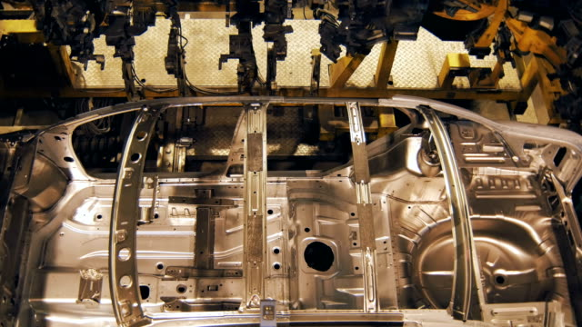 making-car-body-on-a-factory-top-view-robots-are-welding-sparks-and-lights