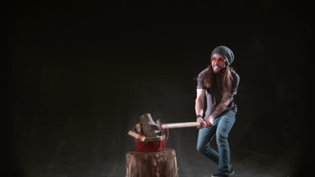 Man-smashing-Christmas-gift-with-hammer-in-slow-motion
