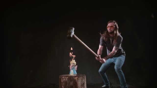 Man-smashing-ceramic-angel-with-hammer-in-slow-motion