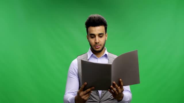 Empresario-serio-Lee-documentos-sobre-clave-pantalla-verde-Chroma-mantener-informes-pensativo