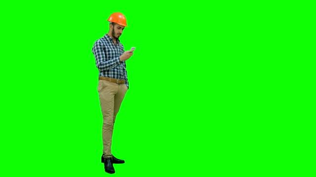 Civil-engineer-in-helmet-using-mobile-phone-on-a-Green-Screen-Chroma-Key