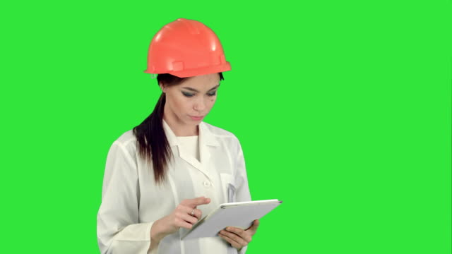 Female-engineer-in-helmet-using-tablet-computer-on-a-Green-Screen-Chroma-Key