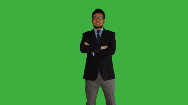 Young-Asian-Businessman-in-Front-of-a-Green-Screen-Talking-Turning-Around-and-Smiling-Symbolizing-Growth-Finance-Bank-Banker-Success