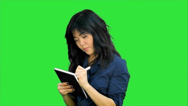 Mujer-asiática-pensativa-hace-algunas-notas-en-Bloc-de-notas-en-una-pantalla-verde-Chroma-Key