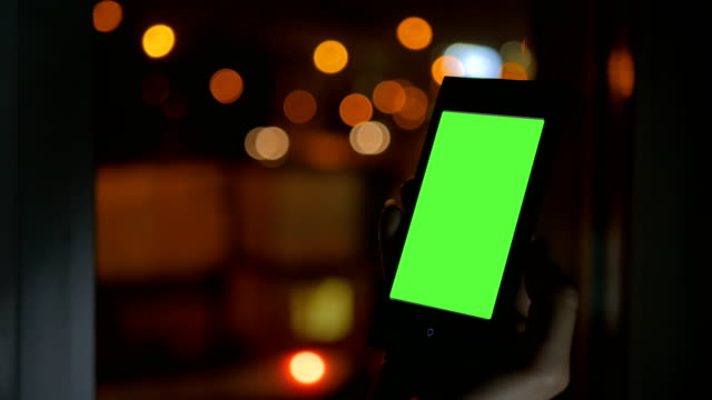 Woman-looking-at-smartphone-with-green-screen