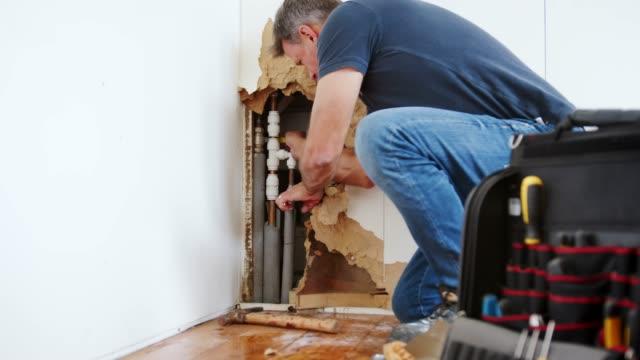 Domestic-Plumber-With-Tools-Repairing-Leaking-Pipe