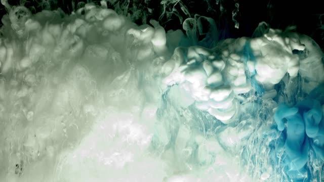 Nube-de-pintura-acrílica-azul-y-blanco-rociado-de-agua-sobre-fondo-negro-