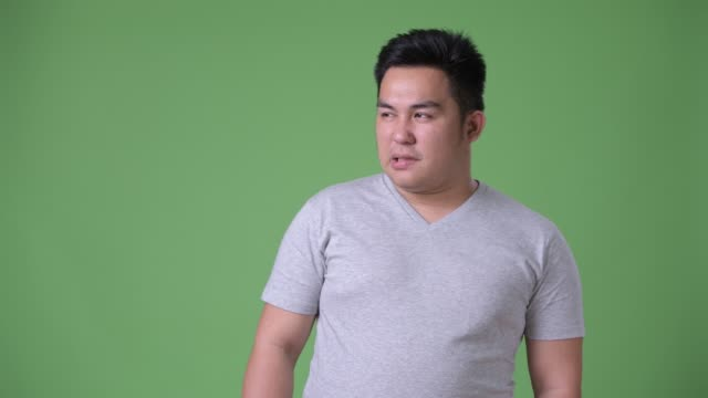 Young-handsome-overweight-Asian-man-against-green-background