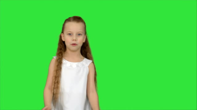 Cute-little-girl-singing-a-song-and-dancing-on-a-Green-Screen-Chroma-Key