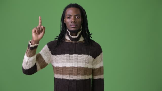 Young-handsome-African-man-with-dreadlocks-against-green-background