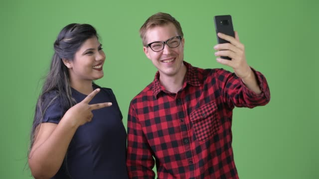 Young-multi-ethnic-business-couple-together-against-green-background