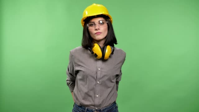 Young-pretty-builder-woman-standing-in-earphones-glasses-and-helmet-with-hands-in-pockets-and-looking-in-camera-chroma-key-background