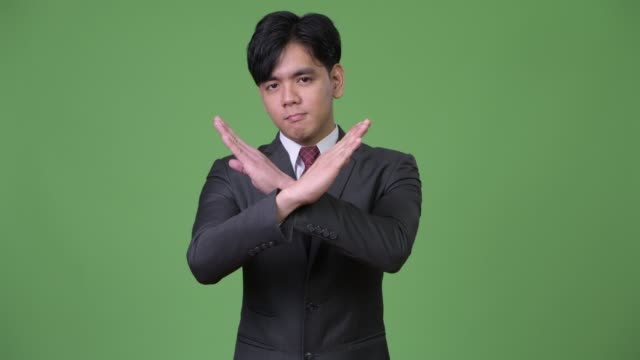 Young-handsome-Asian-businessman-gesturing-to-stop