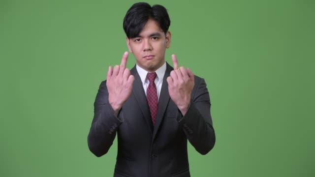 Young-handsome-Asian-businessman-showing-middle-fingers