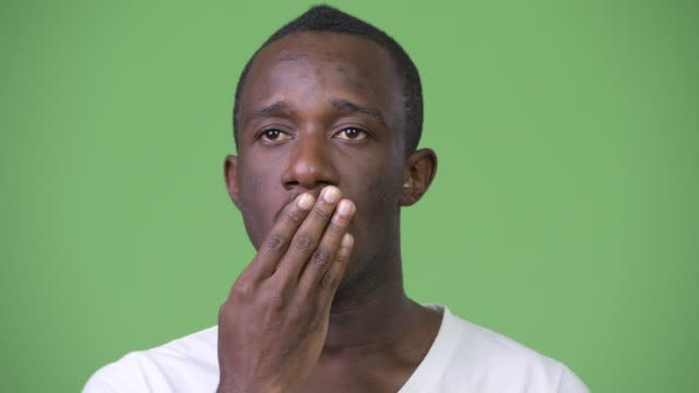 Young-African-man-looking-shocked-and-guilty-against-green-background